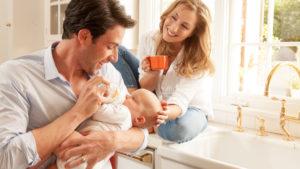 Parents bottle feeding baby Munchkin branding